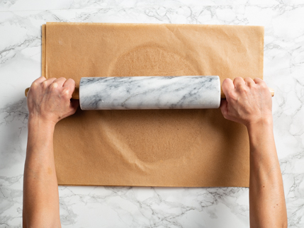 Rolling dough between sheets of parchment with a rolling pin