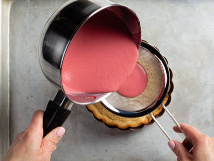 Pouring raspberry-rosewater panna cotta through a strainer into baked tart shell