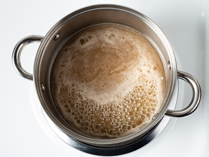 Simmering sugar in a pot on a stove