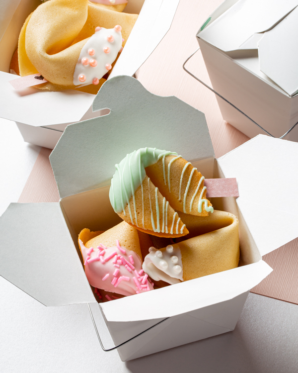 Fortune cookies dipped in icing and decorated with sprinkles in Chinese food boxes