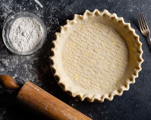 Unbaked pie crust with a bowl of flour, a rolling pin, and a fork