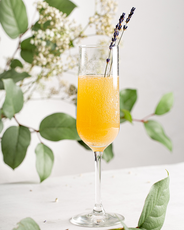 A tall glass of Lemon Lavender Mimosa garnished with fresh lavender sprigs with greenery and flowers in the background