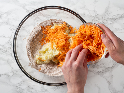 Adding grated sweet potatoes to a bowl of mashed potatoes and dry ingredients
