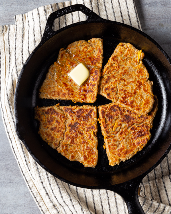 Sweet potato farls in a cast-iron skillet with a pat of butter