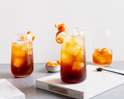 Three glasses of Orange Cold Brew Coffee Spritz with ice and garnished with orange peel.
