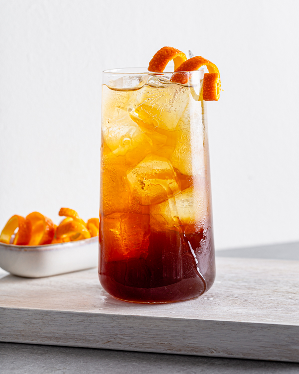 One glass of Orange Cold Brew Coffee Spritzer with ice and garnished with orange peel shown with a dish of curly orange peel strips