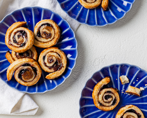 Three blue plates with blueberry pie crust pinwheels (pets des soeurs) on a white surface