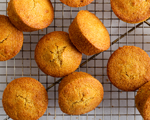 Cornmeal Muffins on a wire cooling rack with a light green cloth