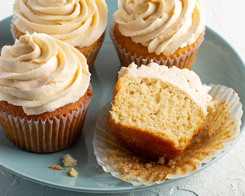 Four iced vanilla cupcakes on a plate, one cut in half