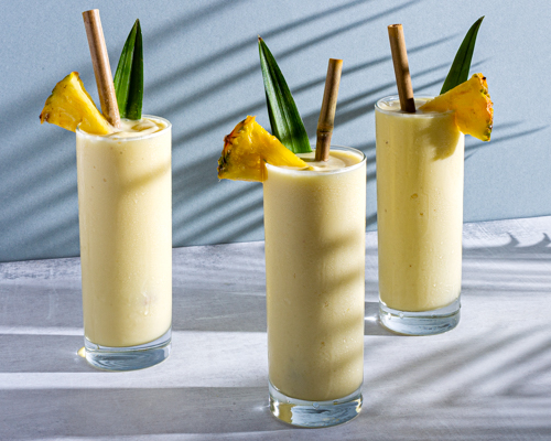 Three glasses of Piña Colada garnished with pineapple spears and leaves, with bamboo straw