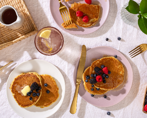 three plates of pancakes garnished with summer berries on a table with gold cutlery, with more berries and syrup on the side