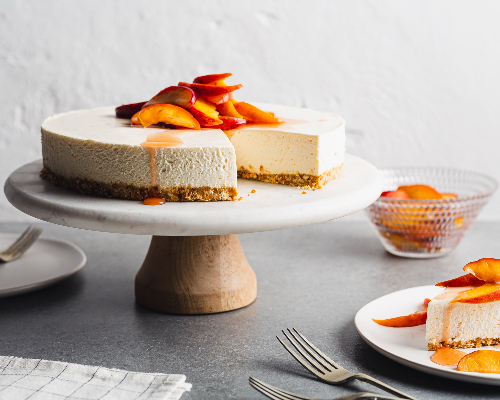 No-bake vanilla cheesecake with peach topping on a cake stand with a slice served on a plate.