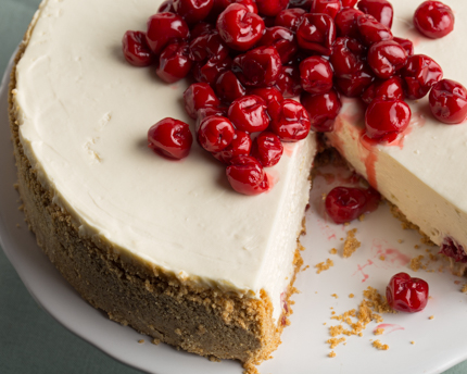 A cherry cheesecake with a slice missing