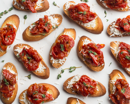 Crostini with tomato jam artfully displayed with fresh herbs