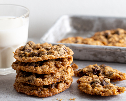 A stack of oatmeal chocolate chip cookies with a glass of milk and a tin serving tray.