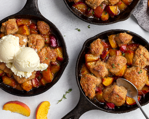 Three peach cobblers served in cast iron frying pans, one with vanilla ice cream