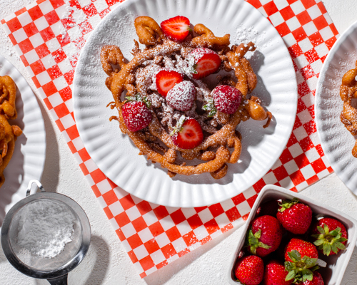 Funnel cake dusted with icing sugar and topped with strawberries on a paper plate