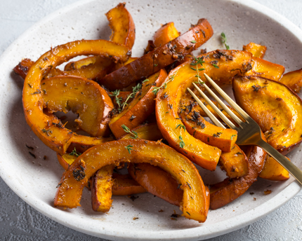 Roasted pumpkin sections in a dish with seasoning