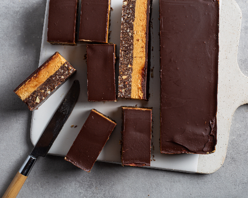 Nanaimo bar cut into slices on a cutting board