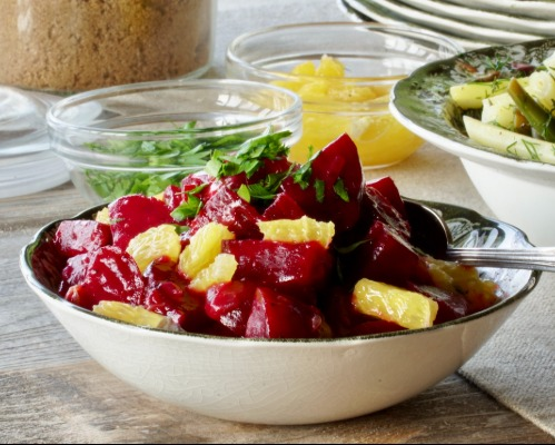 A bowl of orange and glazed beets