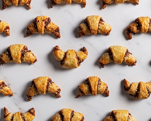 Chocolate tahini rugelach crescents arranged on a marble counter