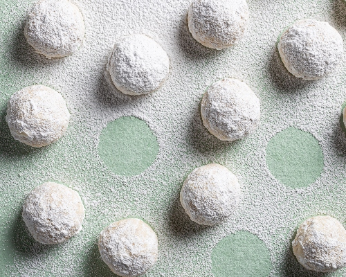 Snowball cookies on a green background, dusted with icing sugar