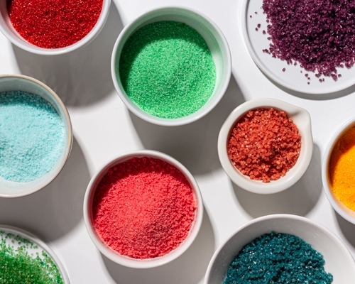 Several bowls of coloured sugar (edible glitter) in different shades and textures