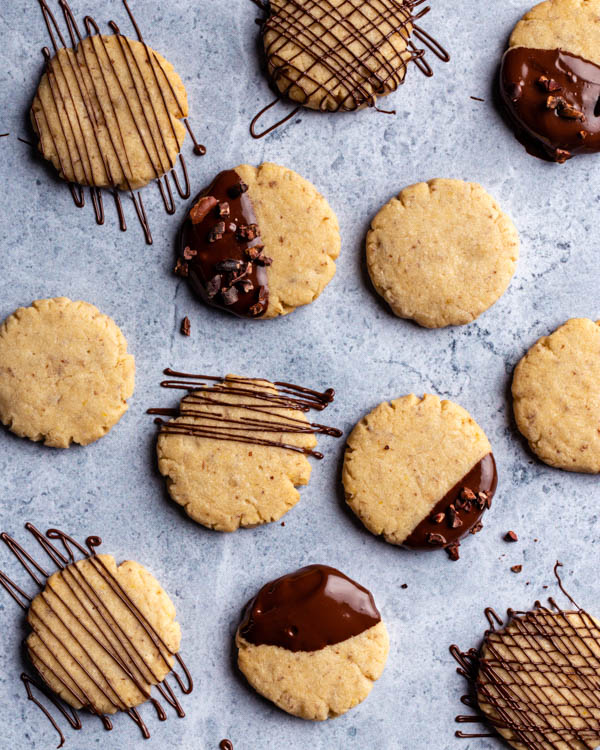 Vegan sugar cookies dipped and drizzled with chocolate on a granite counter
