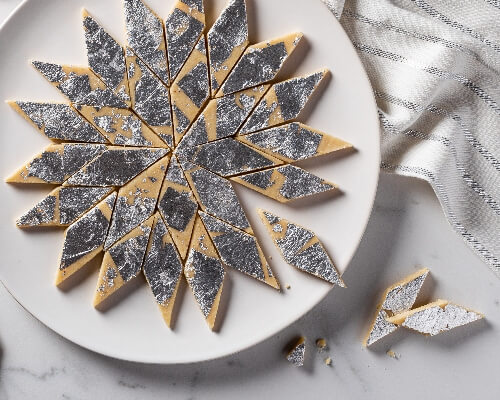 Kaju katli on a plate, cut into diamonds and decorated with silver leaf