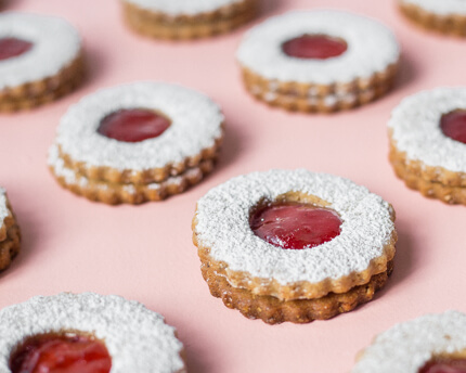 Strawberry Linzer Cookies in rows on a pink background