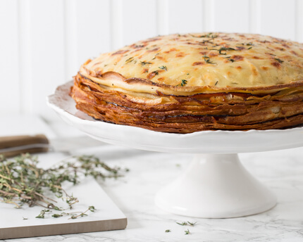 Glazed Ham and Cheese Crêpe Cake on a cake stand