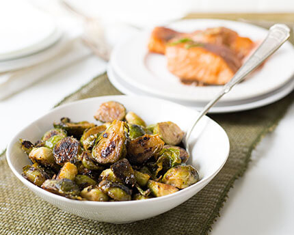 caramelized brussel sprouts in a white bowl with a spoon