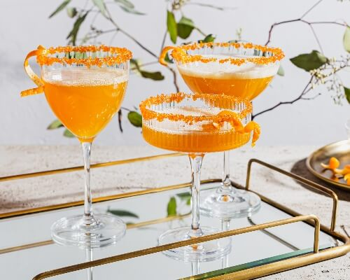 Three glasses of sparkling spiced ginger turmeric cocktail garnished with orange peel and rimmed with sugar on a mirrored tray