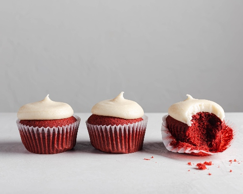 Three Red Velvet Cupcakes with Cream Cheese Frosting lined up, one with the liner peeled and a bite missing