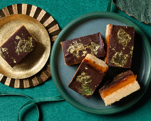 5 millionaire shortbread bars decorated with gold leaf on green plates