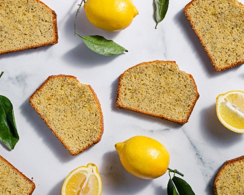 Slices of lemon poppy seed pound cake on a platter with a knife, leaves, and a lemon