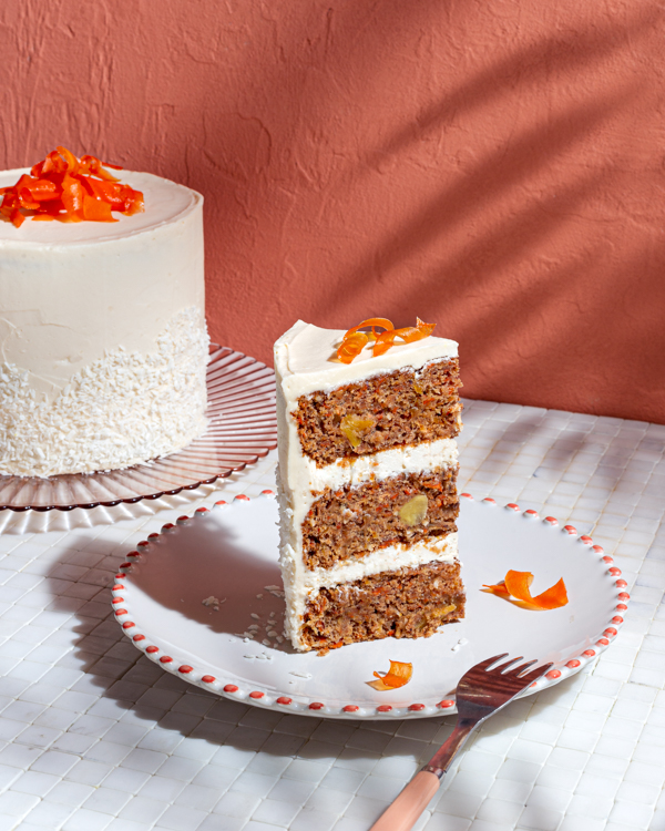 A slice of three-layer vegan carrot cake topped with candied carrot curls on a plate with the full cake in the background