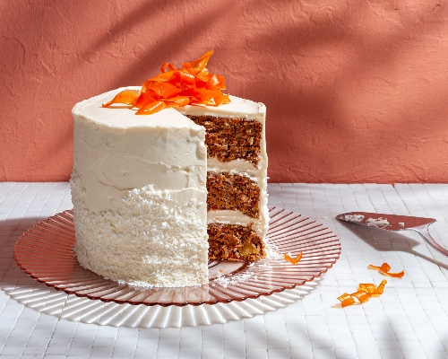 Three-layer vegan carrot cake topped with candied carrot curls on a glass platter