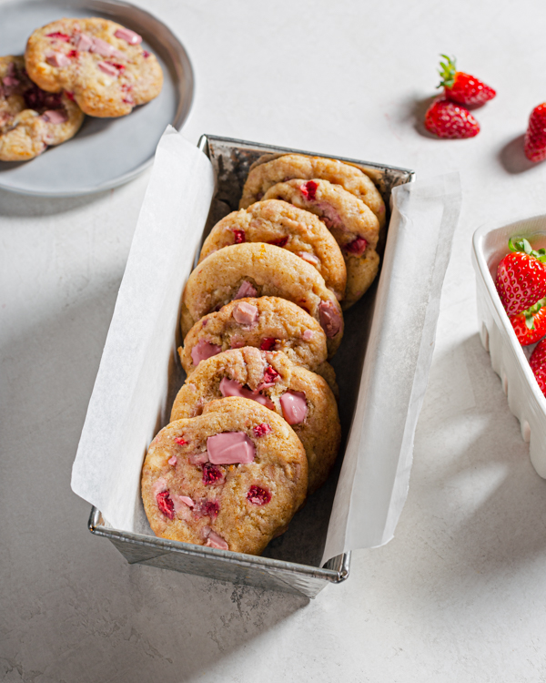 A parchment lined tin filled with strawberry and ruby chocolate chunk cookies
