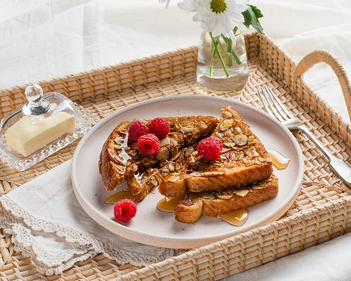 Oat and almond-crusted French toast on a rattan serving tray with butter in a glass dome and flowers in a vase