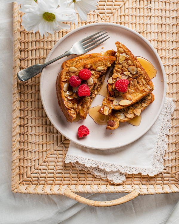 Oat and almond-crusted French toast with syrup on a rattan serving tray with a fork and flowers