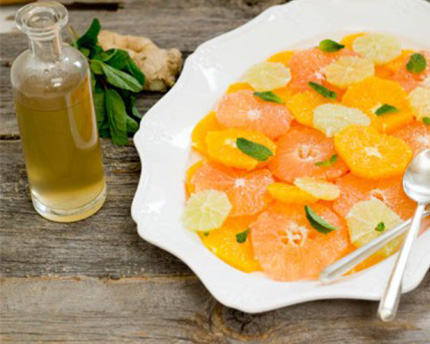 Ginger Mint Citrus Salad in a white bowl with a side of dressing