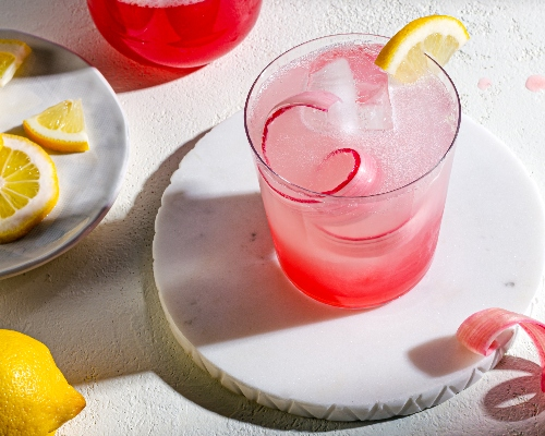 Glass of pink rhubarb lemonade on a coaster garnished with lemon and rhubarb, and a plate of lemon wheels