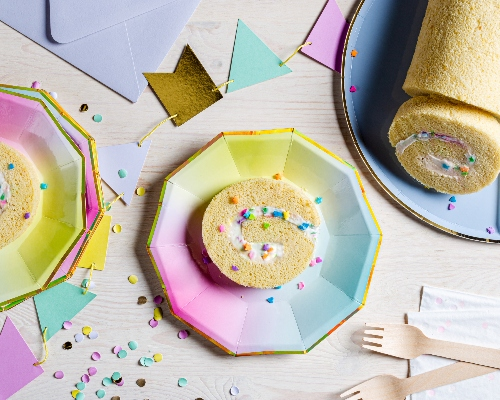 White cake roll on a plate with three slices cut, shown on ombre rainbow plates with wooden forks