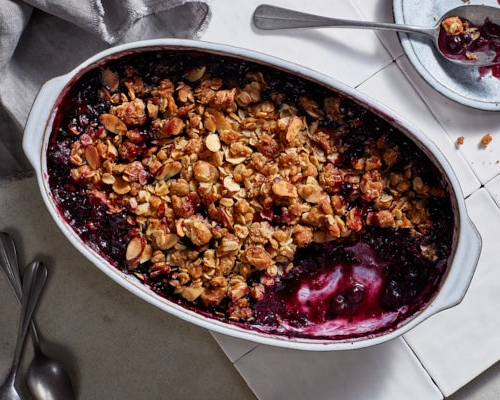 Serving dish full of blueberry crisp with a small amount scooped out on a tile counter