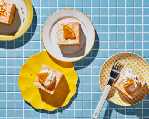 Four pieces of orange vanilla ice cream cake on plates on a blue tiled counter