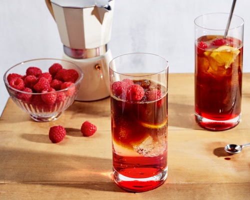 Two glasses of iced raspberry espresso tonic on a wooden table shown with a bowl of raspberries and an espresso maker