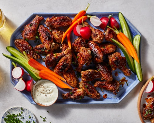A platter of sweet and spicy grilled chicken wings served with raw vegetables, dip, and sparkling beverages