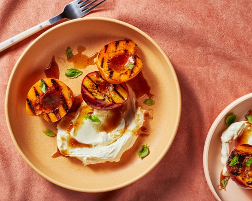 Two bowls of grilled peach halves with mascarpone and basil garnish and brown sugar glaze