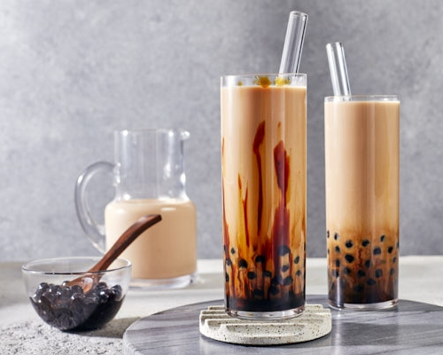 Two glasses of boba hojicha milk tea shown with a pitcher of tea and a bowl of tapioca pearls